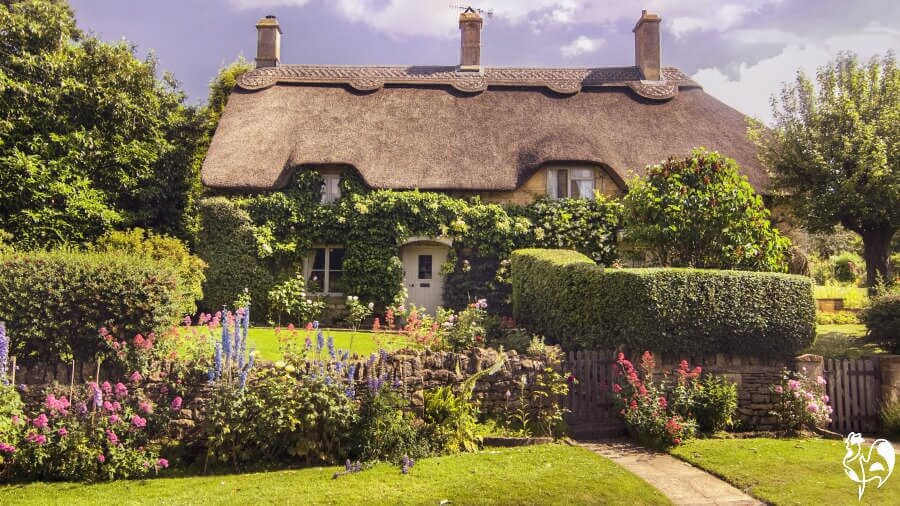 A typical thatched roof country cottage in the Cotswolds, England.