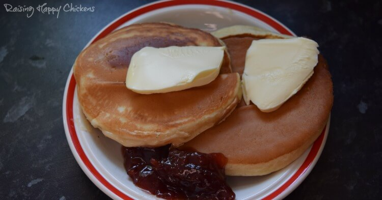 Two Scotch pancakes with butter and jam.