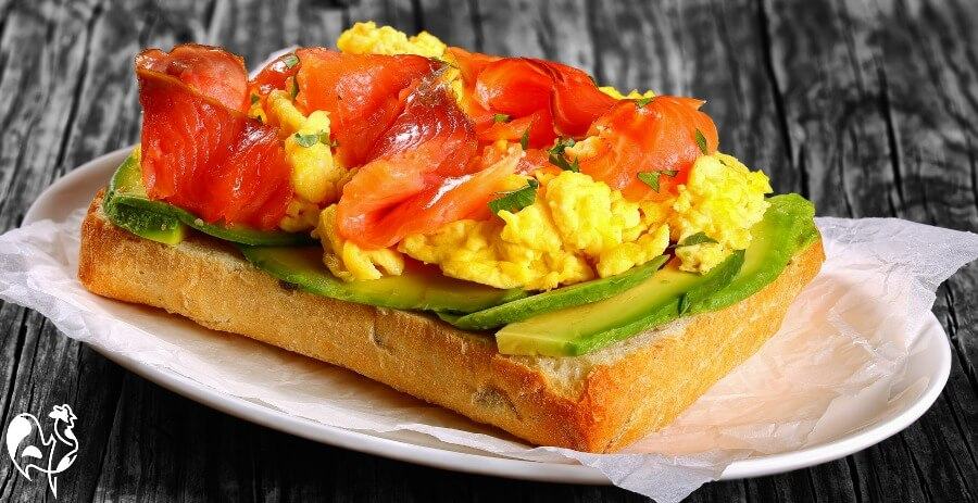 Scrambled fresh eggs with an avocado base and smoked salmon on top.