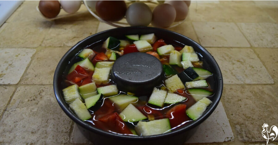 Bundt pan with vegetables ready to be made into a frozen salad treat for my chickens.